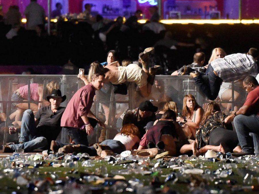 People scramble for shelter at the Route 91 Harvest country music festival, Oct. 1, 2017, in Las Vegas.